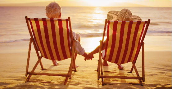 A couple holding hands while reclining in chairs watching sunset on the beach